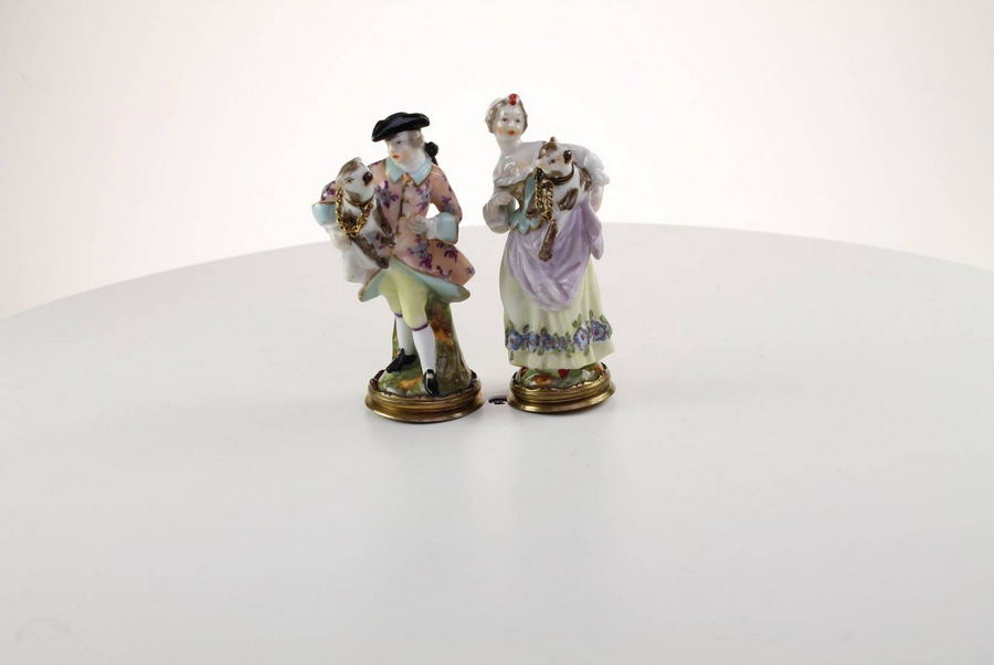 A rare pair of figural perfume bottles of a courting couple holding pugs